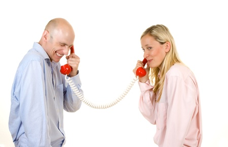 Happy young couple connected with red retro style telephones; white studio background. Stock Photo - 9526307