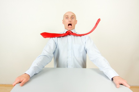 angst: Stressed businessman at table with red tie in midair, studio background.