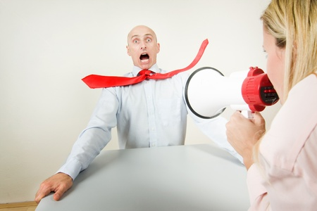 A bullied male worker being blasted by the volume of his bosss megaphone.