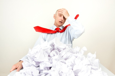 overwhelm: A stressed man holding his head behind a pile of papers.