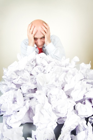 A stressed man holding his head behind a pile of papers. Stock Photo - 9526317
