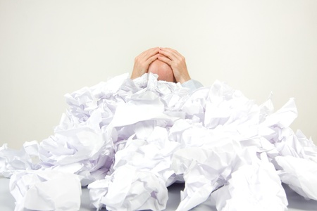 Stressed out man buried in papers holding his head in his hands.  Stock Photo - 9526294