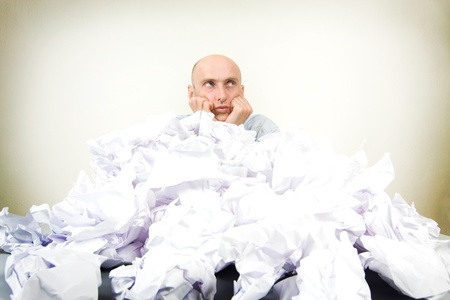 partially: Overworked bald headed male businessman partially buried in paperwork; studio background.