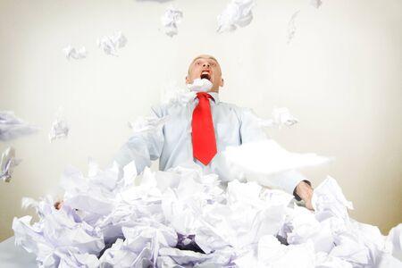 Ein gestresster Geschäftsmann von Papieren begraben.