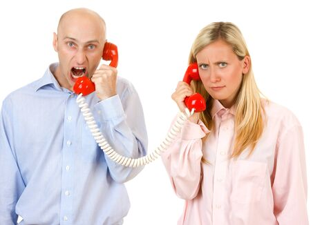 Upset man yelling at a frightened young woman on a red telephone. photo