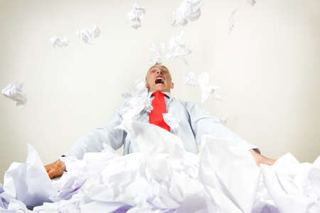 A stressed out businessman being buried by papers. Stock Photo - 9526295
