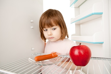 sparse: Girl looking inot an almost empty refrigerator seeing an apple and hot dog.