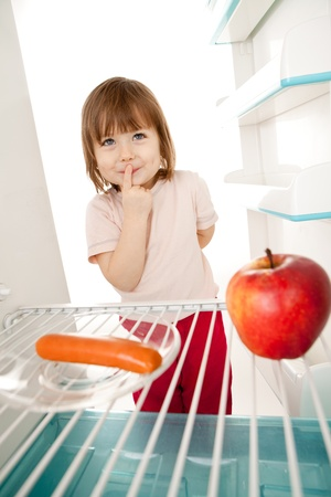 Cute young girl looking in open refrigerator deciding between healthy apple and unhealthy hot dog.