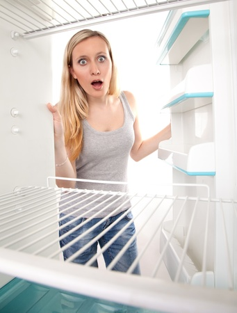 kühl: Attraktive weibliche Teenager in leeren K�hlschrank mit schockiert Ausdruck suchen. Lizenzfreie Bilder
