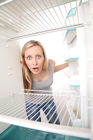 appalled: Attractive female teenager looking in empty refrigerator with shocked expression.