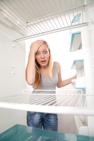 Attractive female teenager looking in empty refrigerator with shocked expression.