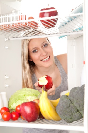 Attractive female teenager eating apple and looking at healthy fruit and vegetables in refrigerator. photo