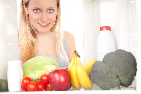 Smiling teenage girl looking inside of a refrigerator with fresh fruits and vegetables. Stock Photo - 9526625
