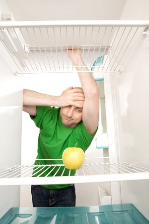 Young man leaning in open doorway of open refrigerator with single apple on empty shelves. photo