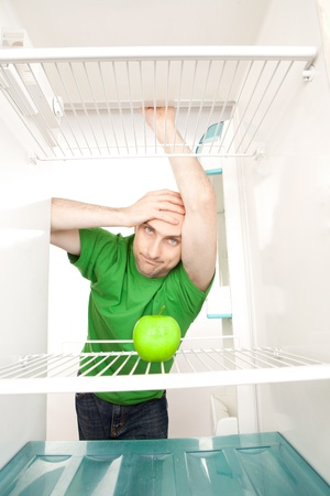 wistful: Young man leaning in open doorway of open refrigerator with single apple on empty shelves.