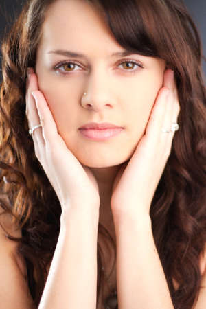 Portrait of a brunette with long brown hair, with her hands on her face. Stock Photo - 9526735