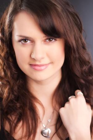 ピアス鼻と長い茶色の髪と美しい若い女の子の肖像画。