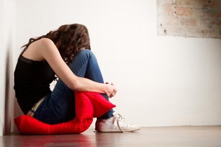 donna che grida: Ha sottolineato la donna sola e seduto sul cuscino rosso raggomitolata.