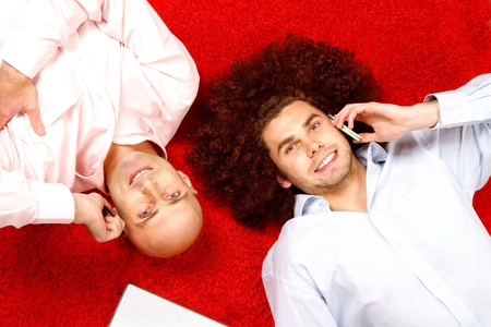 Two men with phones to their ears, laying on their backs in opposite directions on a bright red rug with a pad of paper beside them.  Shot taken from directly above them. photo