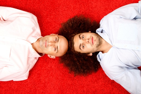 Two young men laying on a red carpet, one is bald and the other has a full head of hair. photo