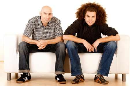 settee: Two happy young male friends relaxing on sofa or settee, white background.