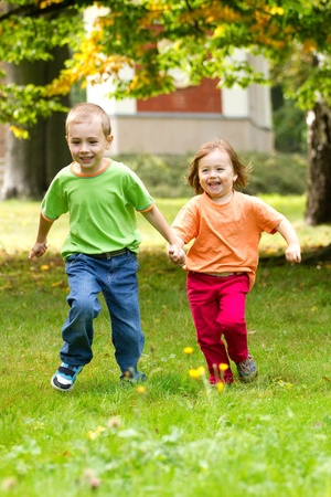 Couple of happy kids running on the grass.