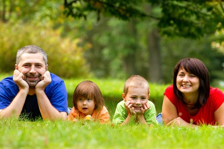 A portrait of a happy family lying on the grass in a park. Stock Photo
