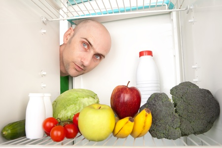 Portrait of young man looking at different healthy food inside refrigerator. photo