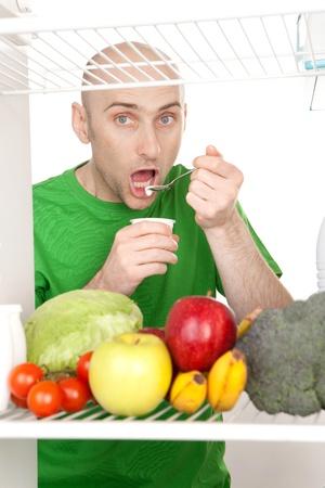 Bald man in green t-shirt eating food.  photo