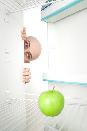 Bald head of young man looking around corner of open refrigerator containing single green apple. photo