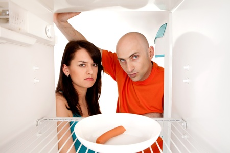 Unhappy young couple looking at single hot dog sausage in otherwise bare fridge. Stock Photo - 9526767