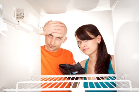 Poor couple with empty wallet looking in bare interior of empty modern refrigerator. photo