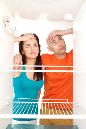 icebox: Man and woman looking into an empty refrigerator. Stock Photo