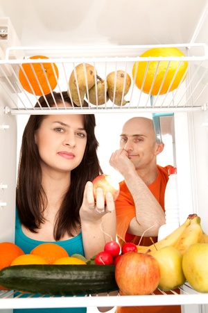 Young couple eating and looking at healthy fruit and vegetable in modern refrigerator, isolated on white background. photo