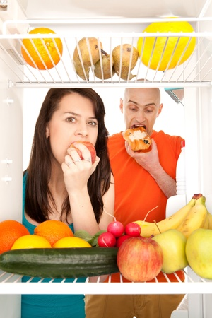Young couple eating and looking at healthy fruit and vegetable in modern refrigerator, isolated on white background. Stock Photo - 9526790