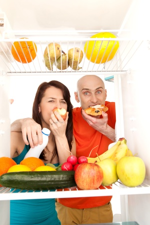A couple eating cream cakes standing in the open door of the refrigerator full of healthy fresh fruit. photo
