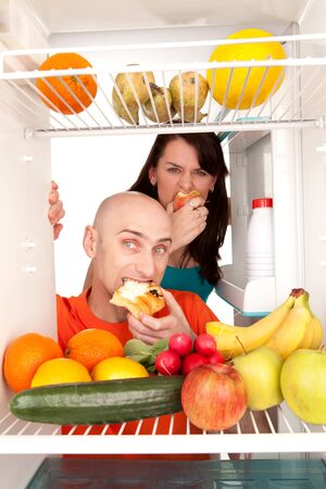 Young couple eating and looking at healthy fruit and vegetable in modern refrigerator, isolated on white background. Stock Photo - 9526786