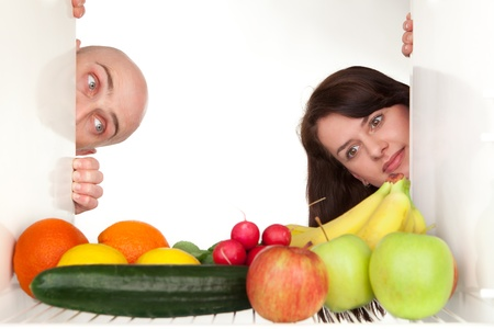 Couple peeping around corner of refrigerator to look at healthy food and vegetables, White background and copy space. photo