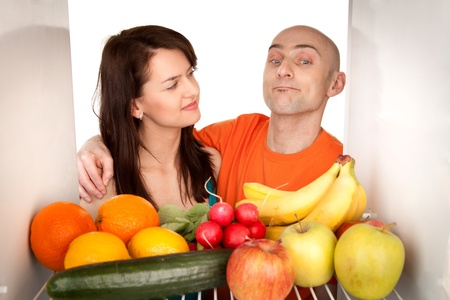 Young couple eating and looking at healthy fruit and vegetable in modern refrigerator, isolated on white background. Stock Photo - 9526783