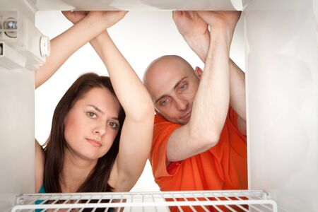 Happy young couple looking in empty refrigerator. Stock Photo - 9526775