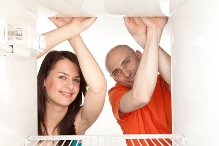 Happy young couple looking in empty refrigerator. Stock Photo - 9526766