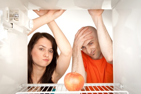 Young couple looking at ripe apple in otherwise empty refrigerator. photo