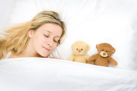 Closeup of pretty blond haired teenager sleeping with teddy bears in bed.