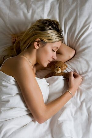 Closeup of pretty blond haired teenager sleeping with teddy bear in bed. photo