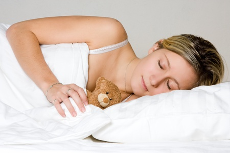 Portrait of blond haired teenager sleeping with teddy bear toy, light studio background. photo