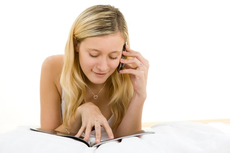 Portrait of blond haired teenager relaxing with magazine and mobile telephone, white background. Stock Photo - 9574664