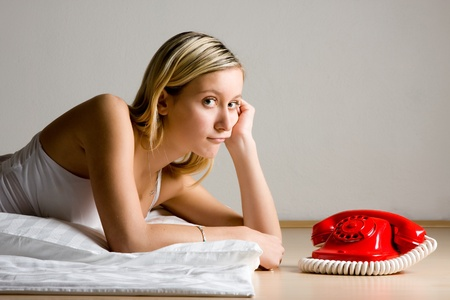 A pretty, blond teenager, laying on her stomach, looking at a old fashioned, red, rotary telephone. photo