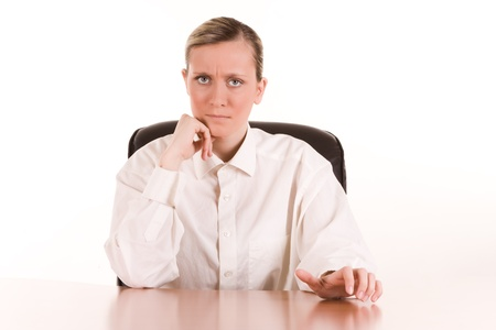 authoritative woman: Portrait of angry young businesswoman at desk with white studio background. Stock Photo