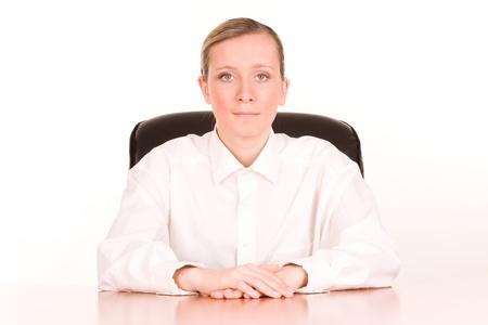 authoritative woman: Portrait of young businesswoman at desk, white studio background.
