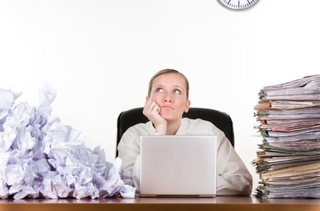 Thinking businesswoman with stack of paperwork, pile of crumpled papers and a laptop computer. Stock Photo